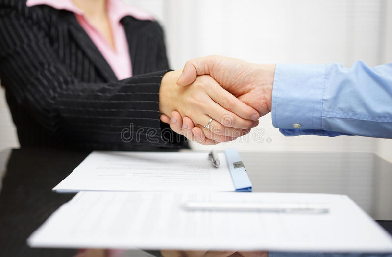 Business partner and client are handshaking over signed contrac royalty free stock image