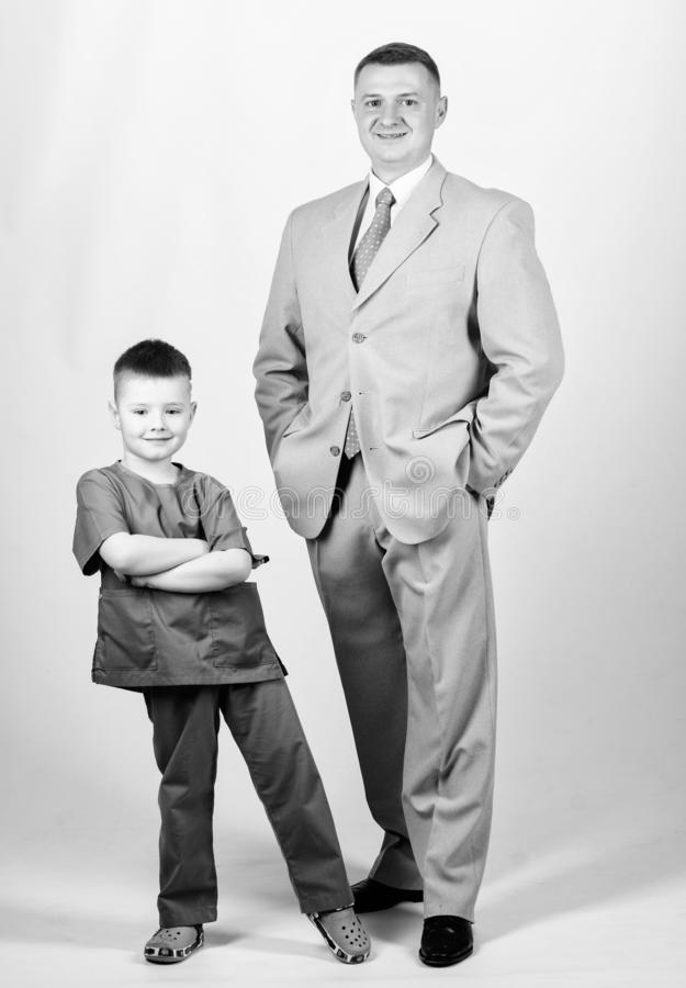 Business partner. small boy doctor with dad businessman. childhood. trust and values. fathers day. family day. father. And son in business suit. male fashion royalty free stock photos