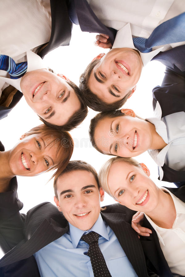 Business partners. Below view of several smart colleagues looking at camera with smiles royalty free stock photography