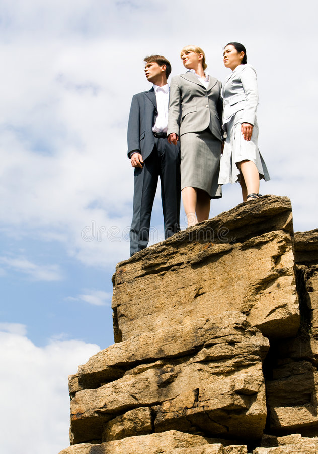 Business partners. Portrait of business group standing on the mount peak and looking into the distance on the background of sky royalty free stock photography