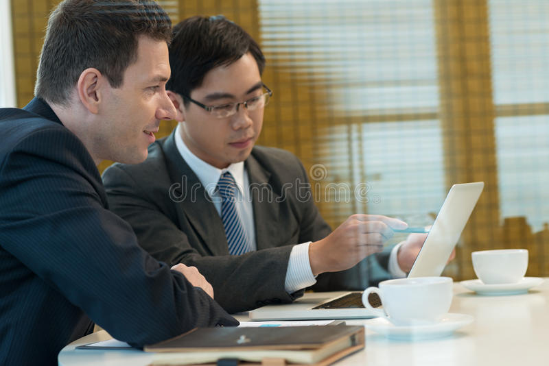 Business partners. Businessman showing some information on the laptop screen to his partner stock image