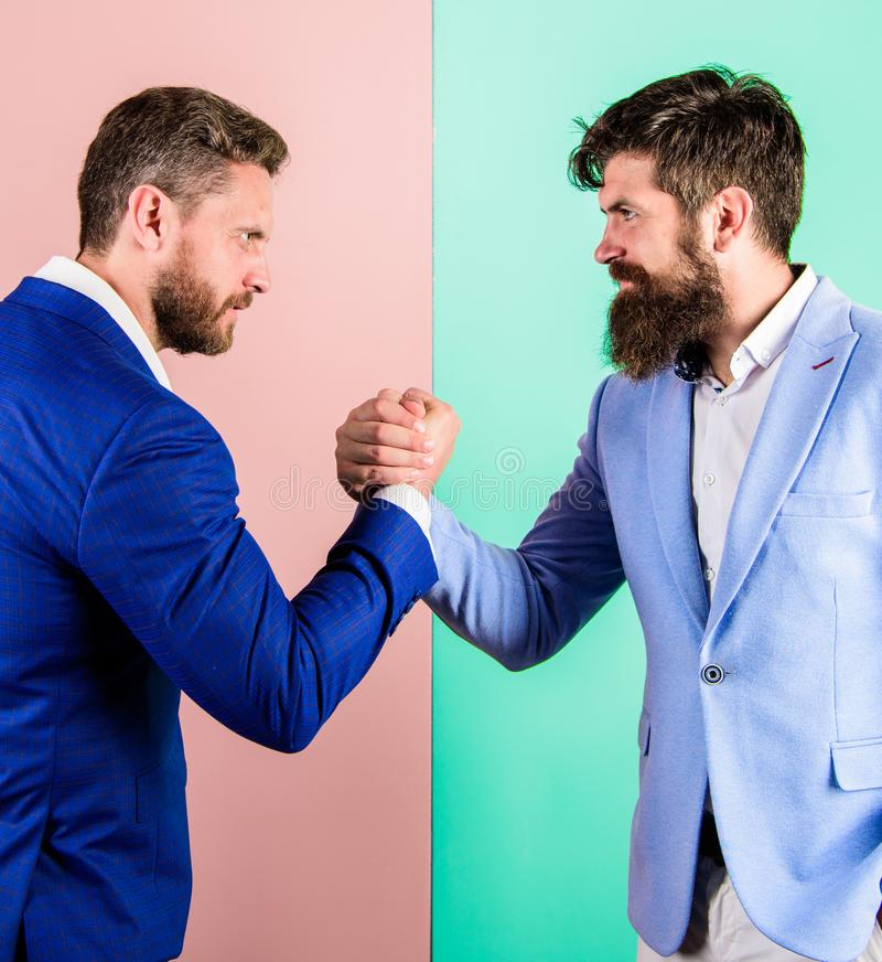 Business partners competitors office colleagues tense faces ready to compete in arm wrestling. Hostile or argumentative royalty free stock photography