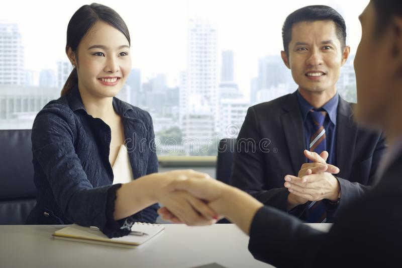 Business partners confirm corporate relationship concept. Young asian businesswoman shaking hands with supplier, finishing up a stock image