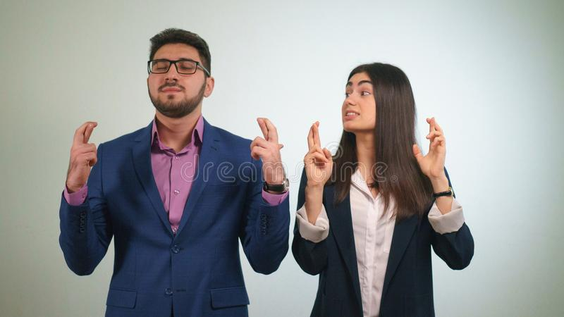 Business partners crossed their fingers the girl looks at her colleague who has closed eyes happily raised his head in royalty free stock image