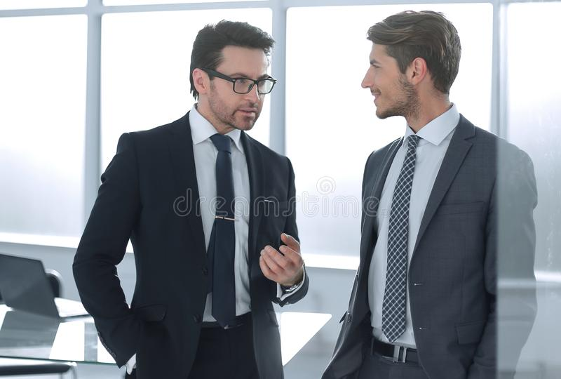 Business partners discuss standing in the office royalty free stock photo