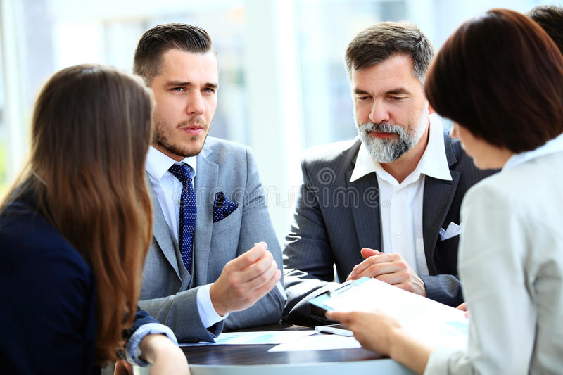 Business partners discussing documents and ideas at meeting royalty free stock photos