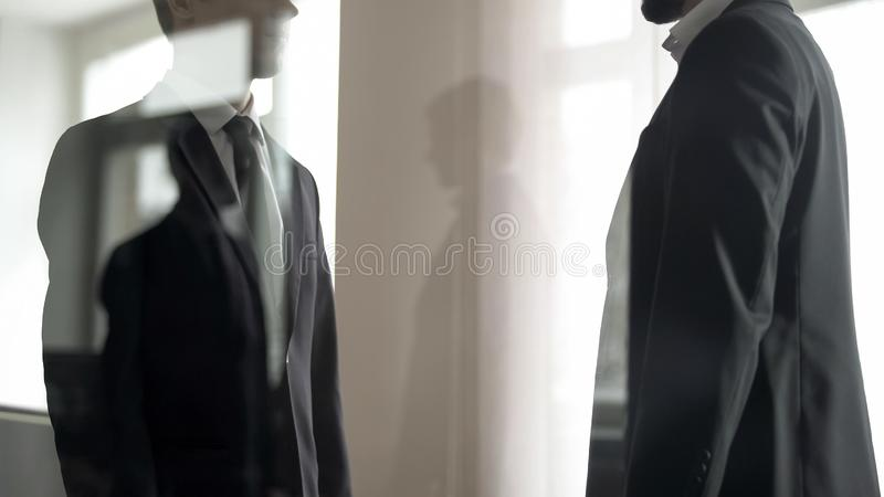 Business partners discussing illegal deal in office lobbying, view through glass. Stock photo stock photo
