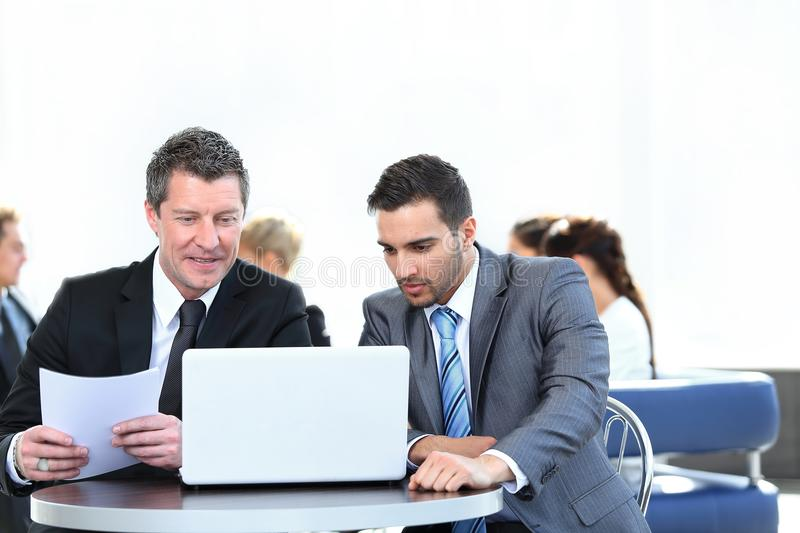 Business partners discussing a new project, sitting in the lobby of the office. stock images