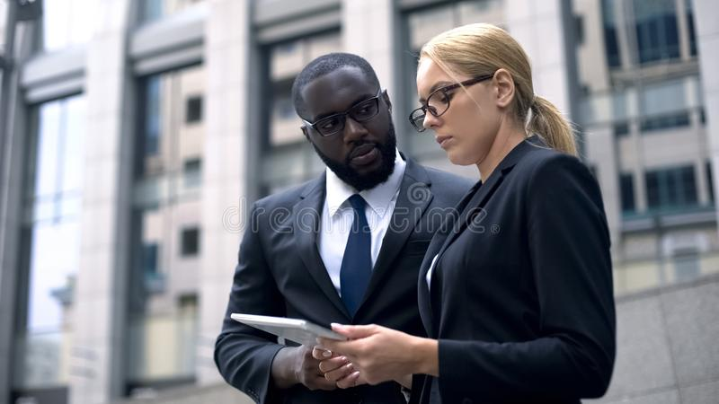 Business partners discussing project on tablet, modern technologies, investor. Stock photo stock photo