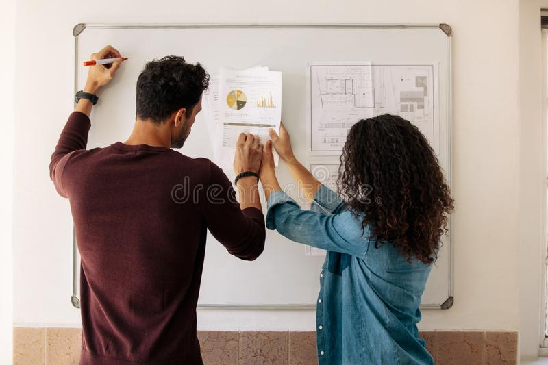 Business partners discussing work on a whiteboard in office royalty free stock images