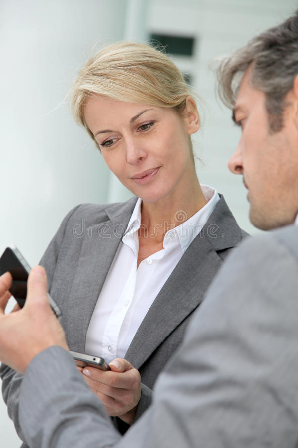 Business partners exchanging numbers stock photo
