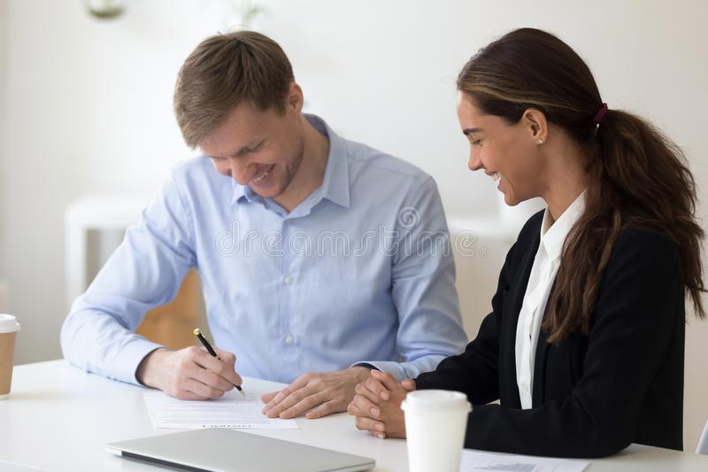 Business partners gathered together for signing contract. Happy biracial businesswoman sitting at desk with business partner people gathered together in office stock photos