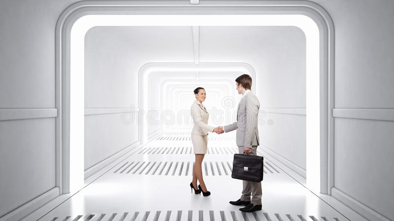 Business partners handshake . Mixed media. Businessman and businesswoman in modern virtual interior shaking hands. Mixed media royalty free stock images