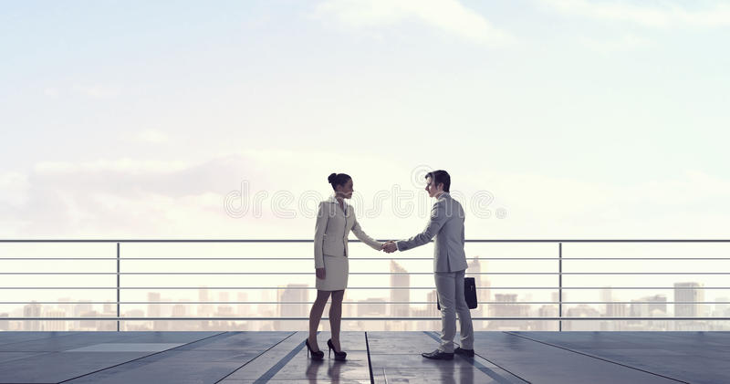 Business partners handshake . Mixed media. Young business people on roof shaking hands to greet each other. Mixed media stock photo