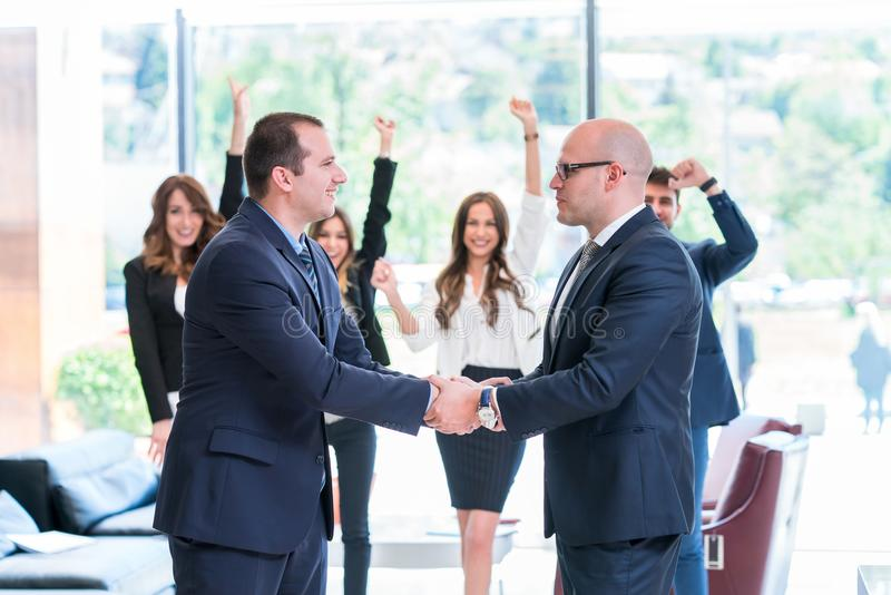 Business partners handshaking after signing contract. Big business deal concluded making everyone happy stock photos