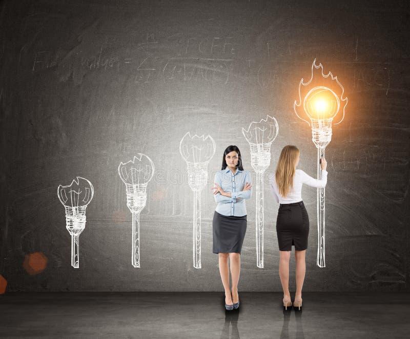 Business partners, light bulb torches, blackboard stock image