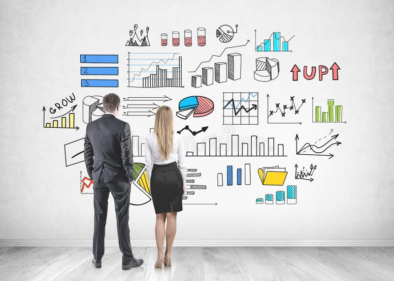 Business partners looking at wall, infographics stock photography