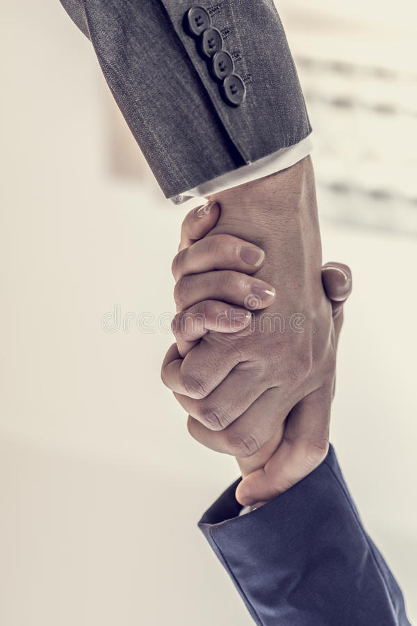 Business partners - man and woman shaking hands to close a deal. Retro image of business partners - man and woman shaking hands to close a deal, in agreement stock image
