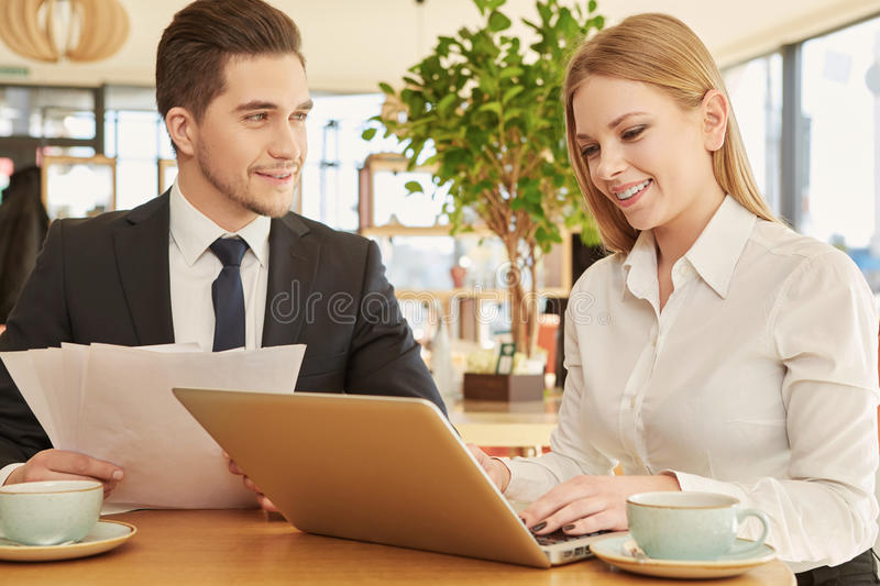 Business partners meeting at the cafe. Admiring partnership. Handsome businessman smiling to his female colleague as she is typing on her laptop at the lunch in stock photo