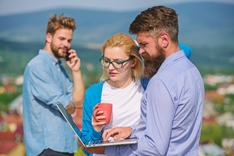 Business partners meeting non formal atmosphere. Colleagues pay attention screen laptop while man talking phone. Colleagues with laptop work outdoor sunny day stock photos