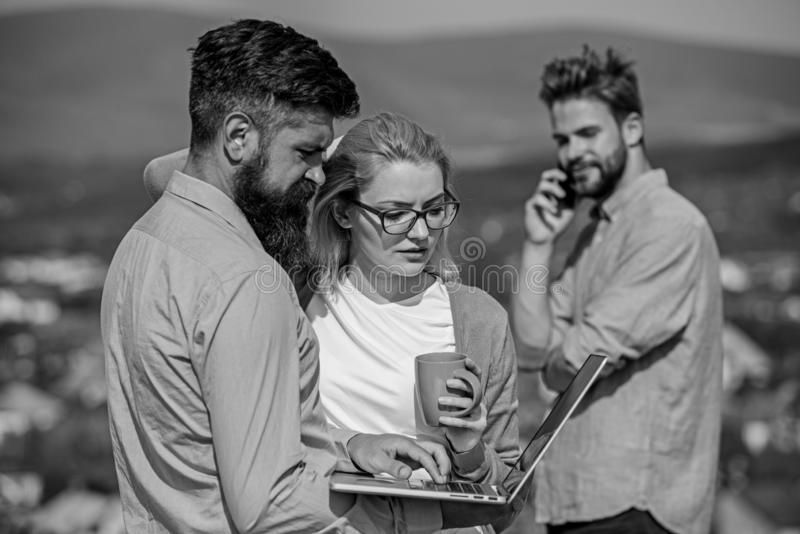 Business partners meeting non formal atmosphere. Colleagues pay attention screen laptop while man talking phone. Business partners meeting non formal atmosphere royalty free stock image