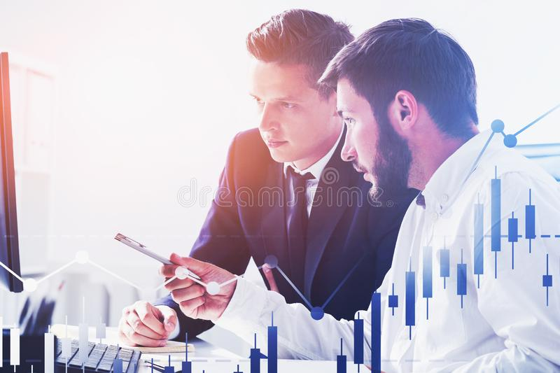 Business partners in office, graphs. Two young business partners discussing work in blurred office with double exposure of graphs. Concept of business growth and stock photography