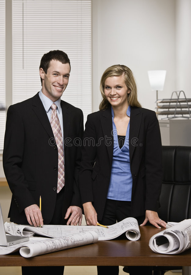 Business partners posing with blueprints royalty free stock photo