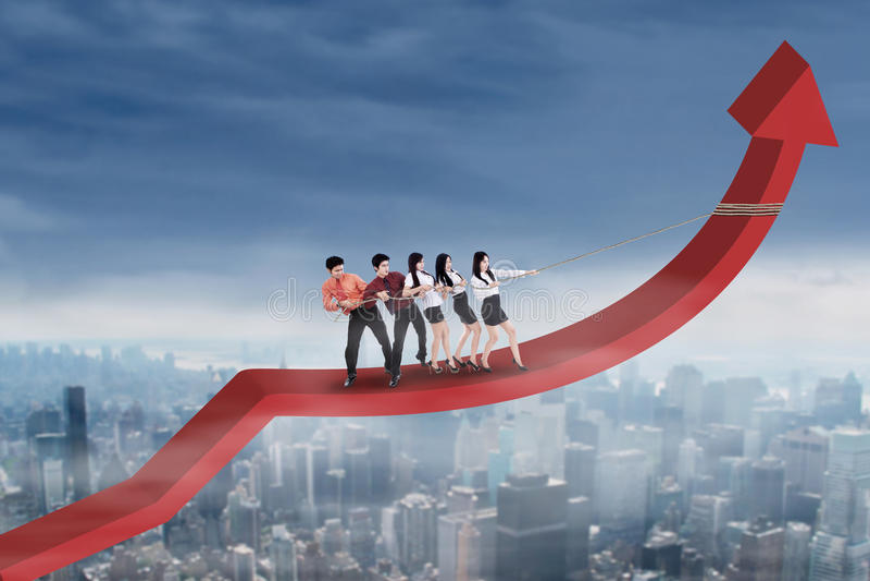Business partners pulling arrow upward. Group of business people standing on arrow and pulling it upward by using a rope stock image