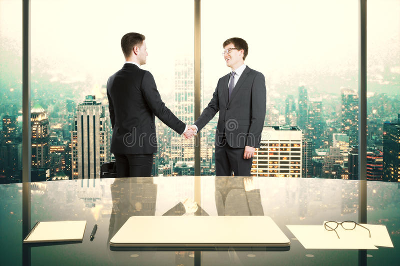 Business partners shake hands in modern office with night megapolis city view royalty free stock photo