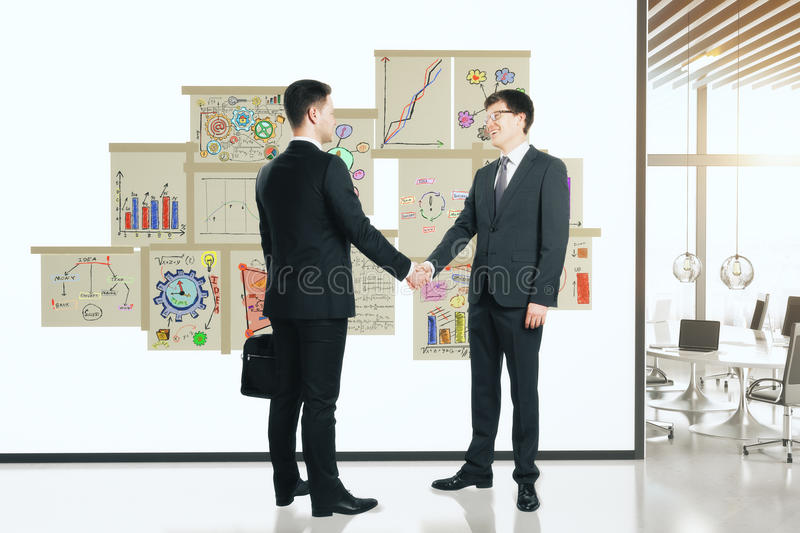 Business partners shake hands at white wall with posters with bu royalty free stock image