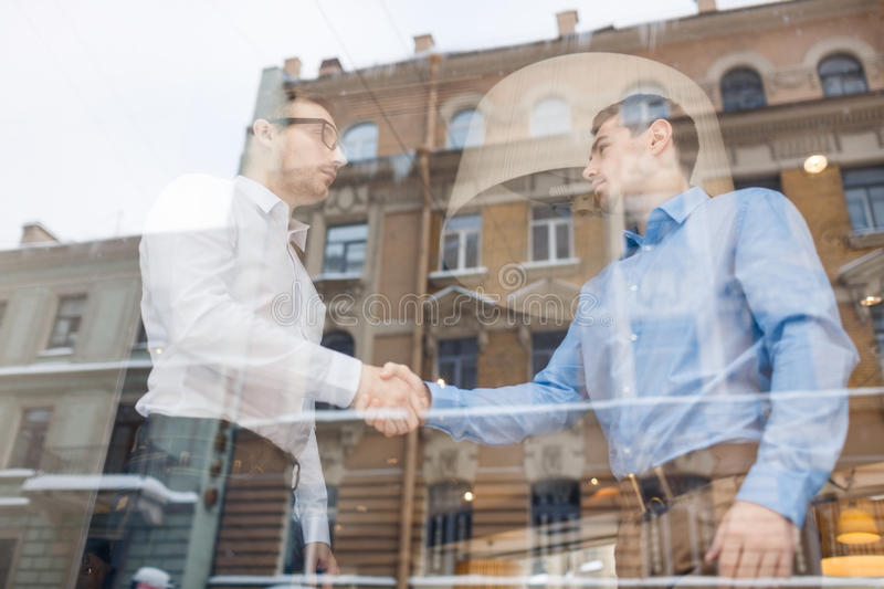 Business Partners Shaking hands Behind Glass Window royalty free stock images
