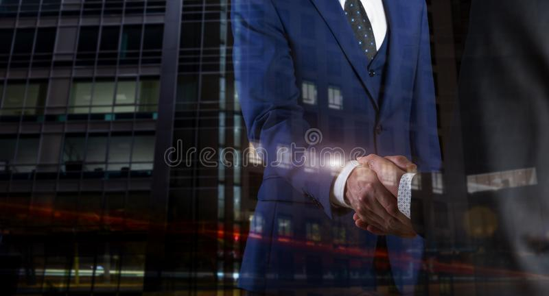 Business people shaking hands on night lights background. Business partners shaking hands on black background stock photography