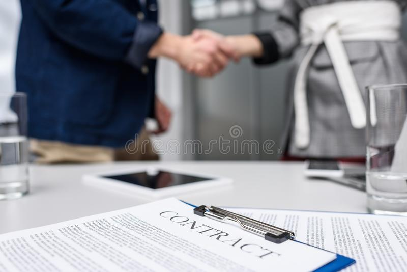 business partners shaking hands with contract on table stock photos