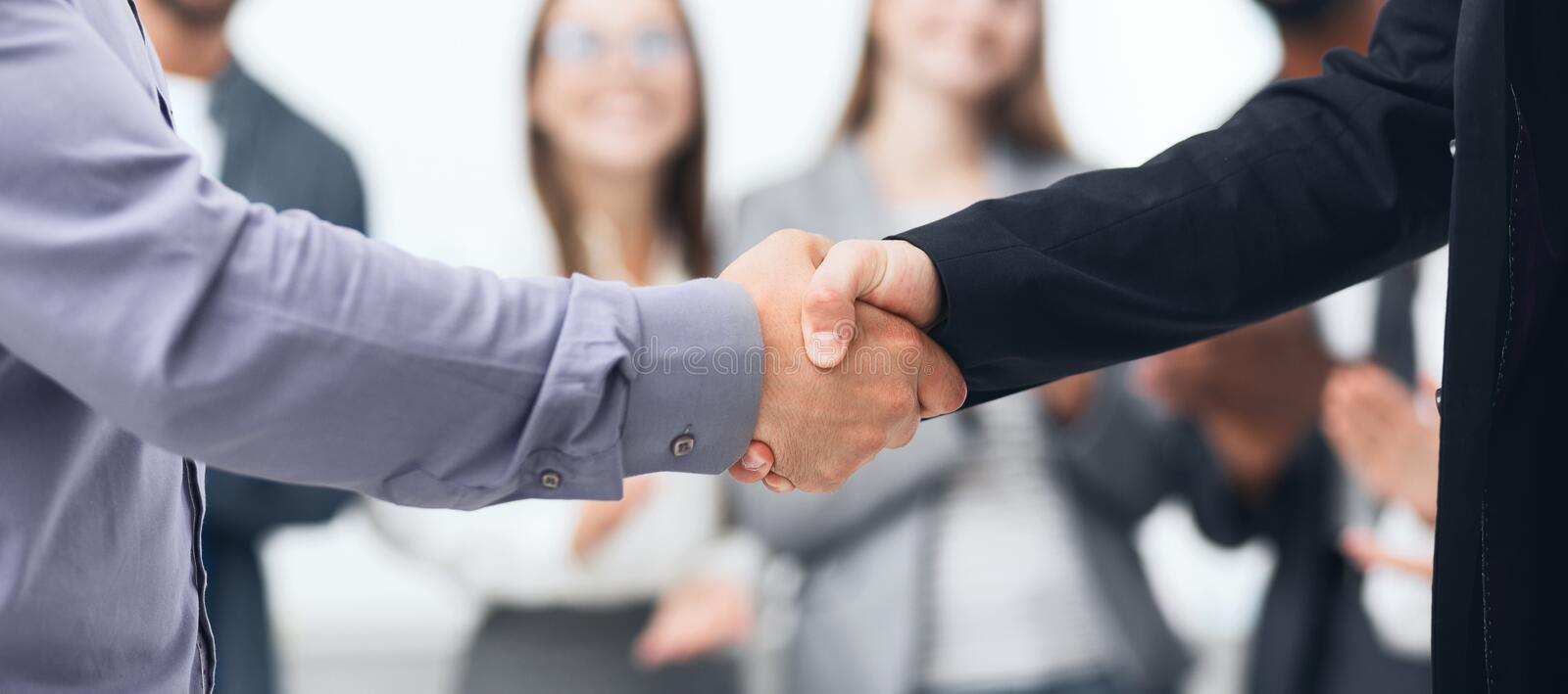 Business partners shaking hands after good deal. In office, crop royalty free stock photo