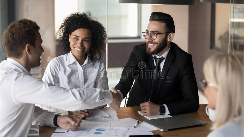 Business partners shaking hands, making agreement at group negotiations stock photography