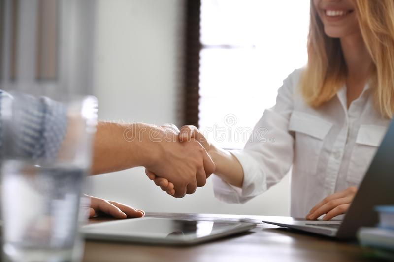 Business partners shaking hands at after meeting in office, closeup stock photography