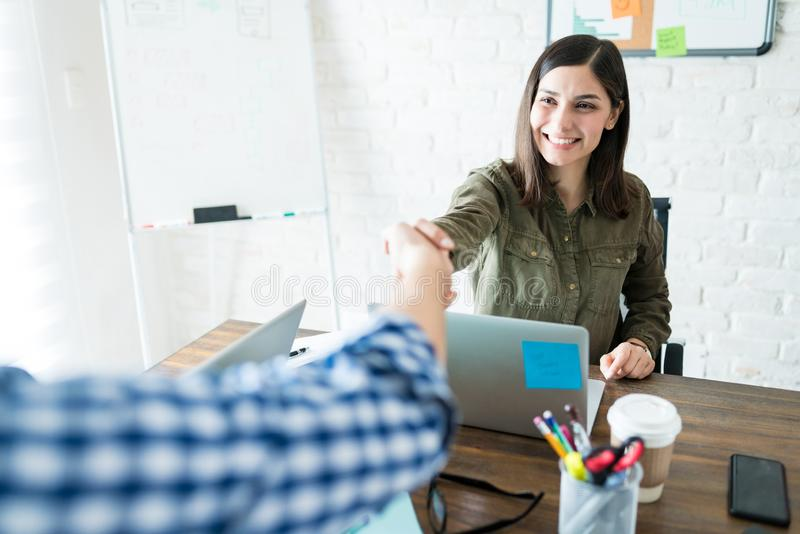 Business Partners Shaking Hands During A Meeting. Smiling businesswoman shaking hands with coworker during office meeting royalty free stock images