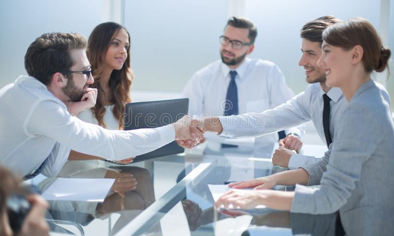 Business partners shaking hands over the Desk. royalty free stock photo
