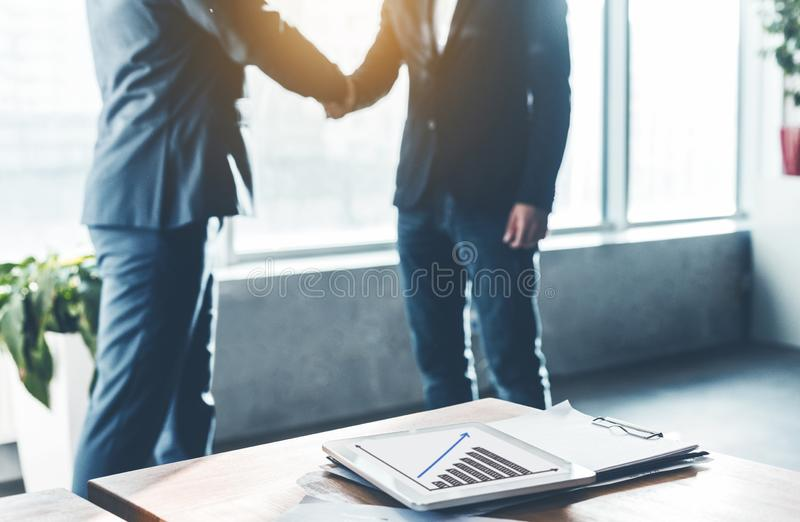 Business partners shaking hands, signing contract in office stock photos