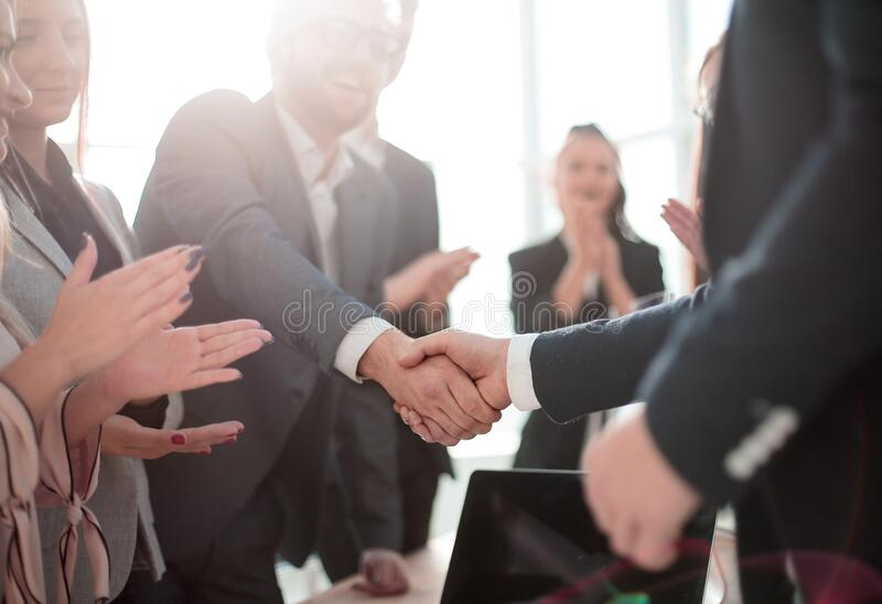 Business partners shaking hands standing in the office. royalty free stock photos