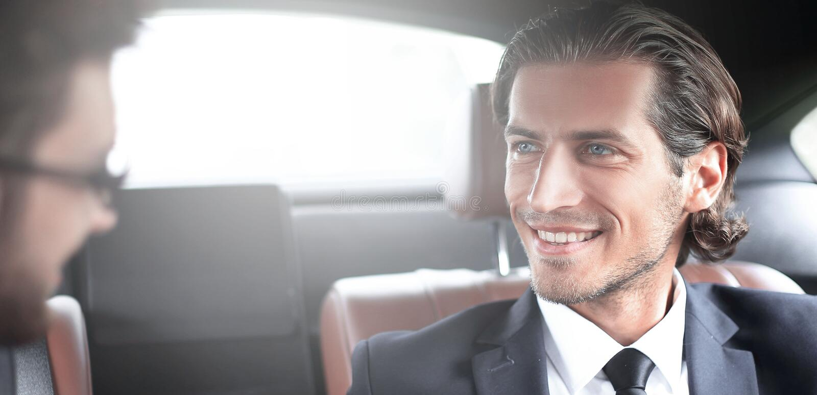 Business partners sitting on the backseat of the car royalty free stock images
