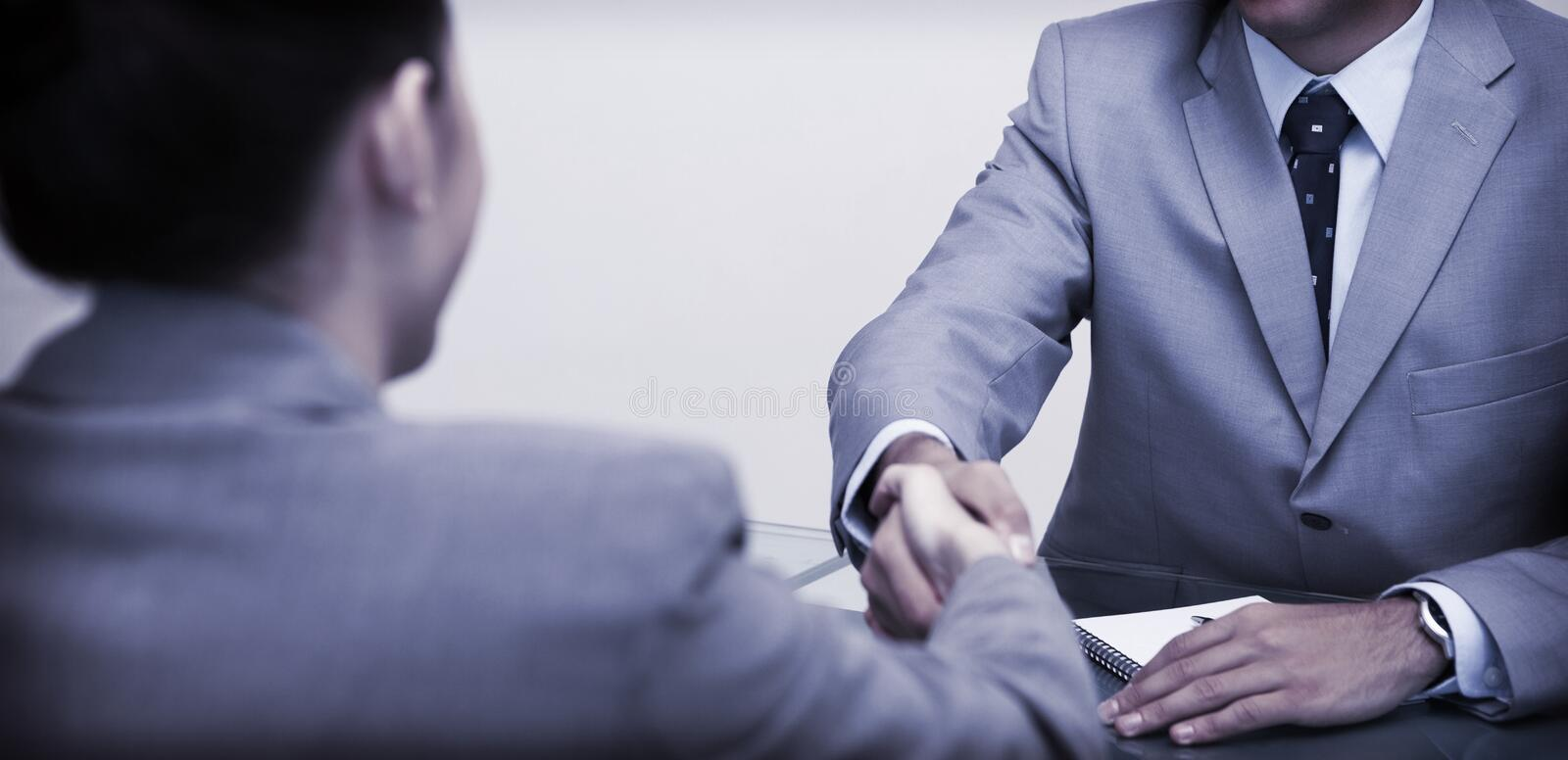 Business partners sitting at a table shaking hands royalty free stock photo
