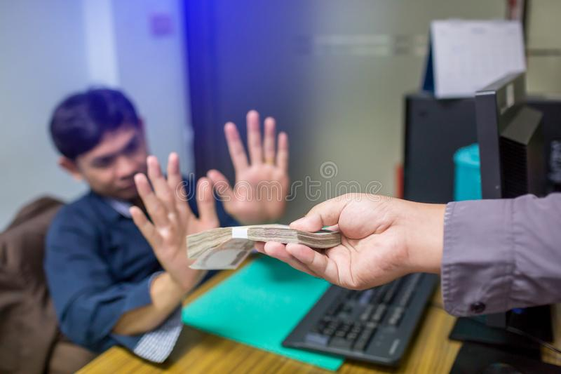Business partners submit fraudulent cash to entrepreneurs whose male businessmen refuse to accept bribes in the office royalty free stock photos