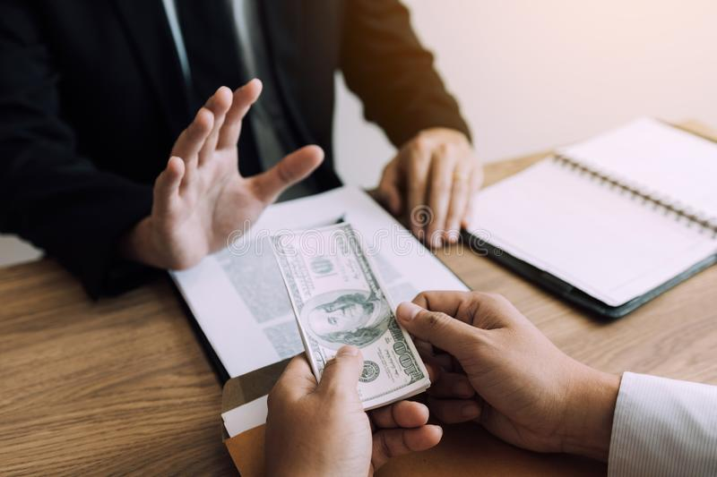 Business partners submit fraudulent cash to entrepreneurs whose male businessmen refuse to accept bribes in the office.  royalty free stock photos