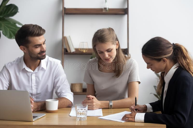 Business partners after successful negotiations signing contract. After successful job interview mixed race female candidate was hired for position signing stock image