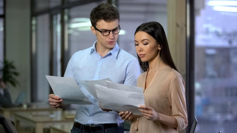Business partners watching papers with graphs, company management, planning stock image