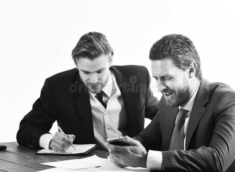 Business partners work with documents and smartphone. Boss gives instructions to employee. Busy people with smiling faces write papers. Boss in formal suit royalty free stock photos