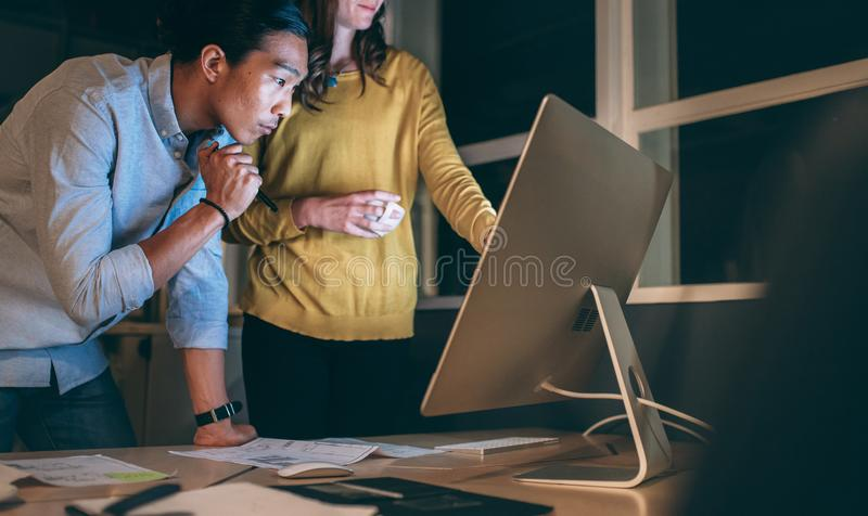Business partners working late night at office. Business colleagues discussing business work late in office. Businessman and women working late in office on royalty free stock photography