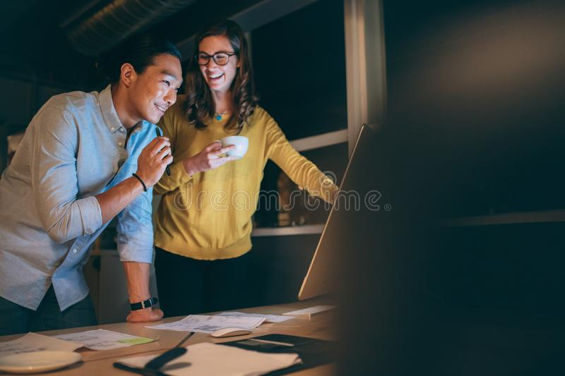 Business partners working late night at office. Business colleagues discussing work late in the night in office. Smiling businessman and women talking to each stock photos