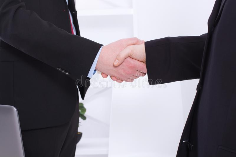 Stylish Successful businessmen handshaking after profitable deal at office background. Image of businessmans handshake in suits royalty free stock photography